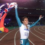 Cathy Freeman carries both the Aboriginal and the Australian flags